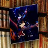Gitarrenspieler vor Büchern